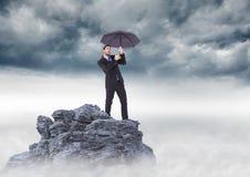 Επιχειρησιακό άτομο που στέκεται στην αιχμή βουνών με την ομπρέλα ενάντια στα θυελλώδη σύννεφα Στοκ φωτογραφία με δικαίωμα ελεύθερης χρήσης