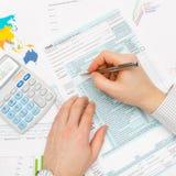 Επιχειρησιακό άτομο που συμπληρώνει τη φορολογική μορφή 1040 ΗΠΑ με τον υπολογιστή δίπλα σε αυτό το αριστερό χέρι - κλείστε επάνω Στοκ Εικόνα
