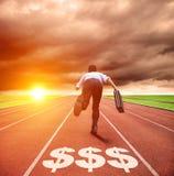 Επιχειρησιακό άτομο που τρέχει στη διαδρομή με το σημάδι χρημάτων στοκ εικόνες