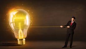 Επιχειρησιακό άτομο που τραβά μια μεγάλη φωτεινή καμμένος λάμπα φωτός Στοκ Φωτογραφίες