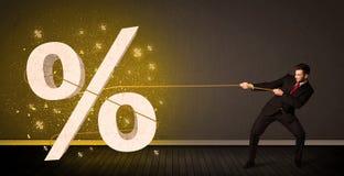 Επιχειρησιακό άτομο που τραβά το σχοινί με το μεγάλο procent σημάδι συμβόλων Στοκ Εικόνα
