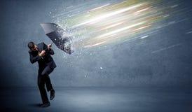 Επιχειρησιακό άτομο που υπερασπίζει τις ελαφριές ακτίνες με την έννοια ομπρελών στοκ εικόνα με δικαίωμα ελεύθερης χρήσης