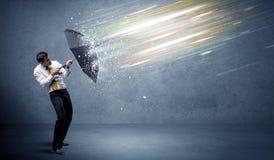 Επιχειρησιακό άτομο που υπερασπίζει τις ελαφριές ακτίνες με την έννοια ομπρελών στοκ φωτογραφίες