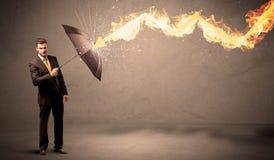 Επιχειρησιακό άτομο που υπερασπίζεται από ένα βέλος πυρκαγιάς με ένα umbrell Στοκ Φωτογραφίες