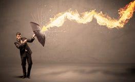 Επιχειρησιακό άτομο που υπερασπίζεται από ένα βέλος πυρκαγιάς με ένα umbrell Στοκ Εικόνα