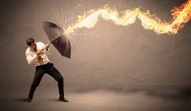 Επιχειρησιακό άτομο που υπερασπίζεται από ένα βέλος πυρκαγιάς με ένα umbrell Στοκ φωτογραφίες με δικαίωμα ελεύθερης χρήσης
