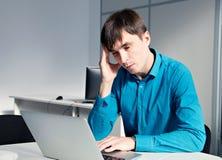 Επιχειρησιακό άτομο που φαίνεται πίεση που λειτουργεί στον υπολογιστή στις υπερωρίες Στοκ Εικόνες