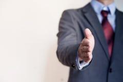 Επιχειρησιακό άτομο που φθάνει έξω στο χέρι στο κούνημα - επιχειρησιακή έννοια και Γ Στοκ Εικόνα