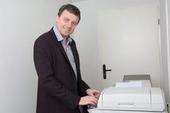 Επιχειρησιακό άτομο που χαμογελά κοντά σε μια μηχανή αντιγράφων Στοκ Φωτογραφίες