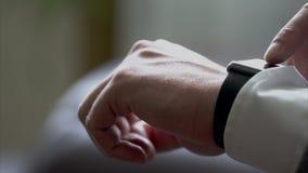 Επιχειρησιακό άτομο που χρησιμοποιεί τα έξυπνα ρολόγια απόθεμα βίντεο
