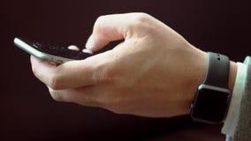 Επιχειρησιακό άτομο που χρησιμοποιεί το κείμενο δακτυλογράφησης smartphone που φορά τα έξυπνα ρολόγια σε ετοιμότητα του φιλμ μικρού μήκους