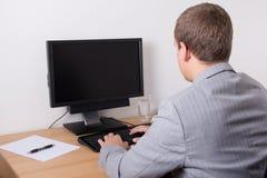 Επιχειρησιακό άτομο που χρησιμοποιεί το προσωπικό Η/Υ στην αρχή Στοκ Φωτογραφία