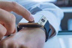 Επιχειρησιακό άτομο που χρησιμοποιεί το smartwatch του app στο καθημερινό φως Στοκ Εικόνα