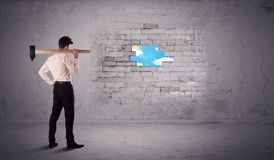 Επιχειρησιακό άτομο που χτυπά το τουβλότοιχο με το σφυρί Στοκ Εικόνες