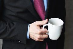 Επιχειρησιακό άτομο σε ένα επιχειρησιακό κοστούμι και ένα φλιτζάνι του καφέ Στοκ εικόνες με δικαίωμα ελεύθερης χρήσης