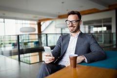 Επιχειρησιακό άτομο σε ένα επιχειρησιακό κοστούμι και ένα φλιτζάνι του καφέ σε ένα γραφείο Στοκ Φωτογραφία