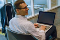 Επιχειρησιακό άτομο στην άσπρη εργασία σε ένα lap-top που χρησιμοποιεί την WI-Fi Διαδίκτυο στον αερολιμένα στοκ φωτογραφίες με δικαίωμα ελεύθερης χρήσης