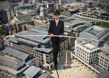Επιχειρησιακό άτομο στην ισορροπία σε ένα σχοινί πέρα από μια πόλη Στοκ Φωτογραφία