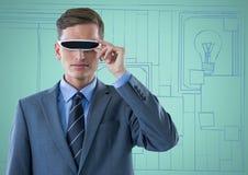 Επιχειρησιακό άτομο στην κάσκα εικονικής πραγματικότητας ενάντια στο συρμένο χέρι τοίχο μπλε και aqua με τις εικόνες Στοκ Εικόνες