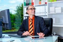 Επιχειρησιακό άτομο στο γραφείο του που φαίνεται φιλικό Στοκ Φωτογραφίες