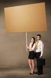 Επιχειρησιακό ζεύγος με το κενό χαρτόνι Στοκ φωτογραφία με δικαίωμα ελεύθερης χρήσης