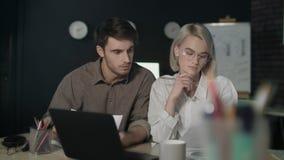 Επιχειρησιακό ζεύγος που εργάζεται στο οικονομικό πρόγραμμα στο σκοτεινό γραφείο από κοινού φιλμ μικρού μήκους