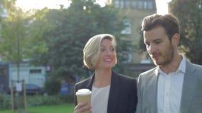 Επιχειρησιακό ζεύγος που περπατά μέσω του πάρκου με το take-$l*away καφέ απόθεμα βίντεο
