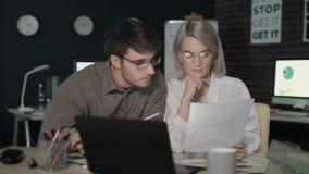 Επιχειρησιακό ζεύγος που προσέχει μαζί τον οικονομικό μπροστινό υπολογιστή εκθέσεων στο σκοτεινό γραφείο απόθεμα βίντεο