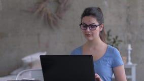 Επιχειρησιακό κορίτσι με τα γυαλιά που λειτουργούν στο σπίτι να καθίσ απόθεμα βίντεο