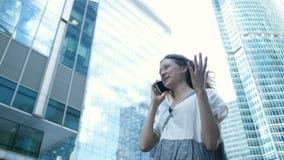 Επιχειρησιακό κορίτσι σε ένα φόρεμα που μιλά στο τηλέφωνο στο υπόβαθρΠφιλμ μικρού μήκους
