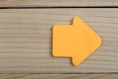 Επιχειρησιακό μέλλον και έννοια κινήτρου - πορτοκαλιά κενή αυτοκόλλητη ετικέττα με μορφή ενός βέλους στο ξύλινο υπόβαθρο στοκ εικόνες
