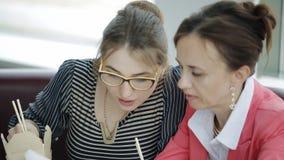 Επιχειρησιακό μεσημεριανό γεύμα δύο όμορφες γυναίκες στο γραφείο Ένα μικρό πρόχειρο φαγητό κατά τη διάρκεια ενός σημαντικού επιχε απόθεμα βίντεο