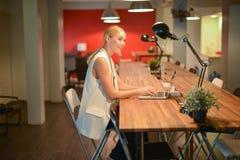 Επιχειρησιακό ξανθό κορίτσι που εργάζεται αργά, χρησιμοποιώντας ένα lap-top σε ένα γραφείο Στοκ φωτογραφία με δικαίωμα ελεύθερης χρήσης