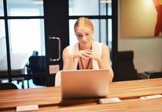 Επιχειρησιακό ξανθό κορίτσι που χρησιμοποιεί ένα lap-top σε ένα γραφείο Στοκ φωτογραφία με δικαίωμα ελεύθερης χρήσης