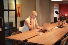 Επιχειρησιακό ξανθό κορίτσι που χρησιμοποιεί ένα lap-top σε ένα γραφείο Στοκ Εικόνες