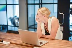 Επιχειρησιακό ξανθό κορίτσι που χρησιμοποιεί ένα lap-top σε ένα γραφείο Στοκ Φωτογραφία