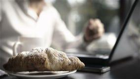 Επιχειρησιακό πρόγευμα με τα croissants, το φλυτζάνι του τσαγιού και το lap-top απόθεμα βίντεο