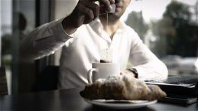 Επιχειρησιακό πρόγευμα με τα croissants, το φλυτζάνι του τσαγιού και το lap-top φιλμ μικρού μήκους