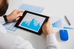 Επιχειρησιακό πρόσωπο που αναλύει τις οικονομικές στατιστικές που επιδεικνύονται στην οθόνη ταμπλετών Στοκ εικόνα με δικαίωμα ελεύθερης χρήσης