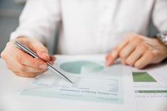 Επιχειρησιακό πρόσωπο που αναλύει τις οικονομικές στατιστικές που επιδεικνύονται στην οθόνη ταμπλετών Στοκ φωτογραφία με δικαίωμα ελεύθερης χρήσης