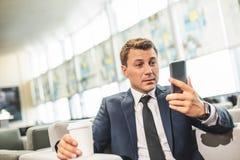 Επιχειρησιακό πρόσωπο που εξετάζει την οθόνη smartphone με την έκπληξη στοκ φωτογραφία με δικαίωμα ελεύθερης χρήσης