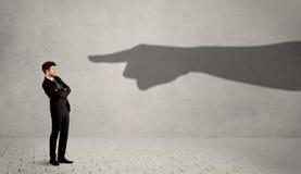 Επιχειρησιακό πρόσωπο που εξετάζει το τεράστιο χέρι σκιών που δείχνει σε τον συμπυκνωμένο Στοκ εικόνα με δικαίωμα ελεύθερης χρήσης