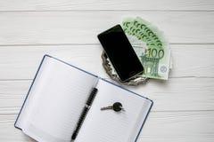 Επιχειρησιακό σύνολο σημείωσης, τηλεφώνου κυττάρων, κλειδιού και χρημάτων σε ένα άσπρο ξύλινο υπόβαθρο Στοκ εικόνα με δικαίωμα ελεύθερης χρήσης