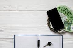 Επιχειρησιακό σύνολο σημείωσης, τηλεφώνου κυττάρων, κλειδιού και χρημάτων σε ένα άσπρο ξύλινο υπόβαθρο Στοκ Εικόνες
