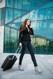 Επιχειρησιακό ταξίδι - γυναίκα με τους περιπάτους βαλιτσών έξω από τον αερολιμένα buil Στοκ εικόνες με δικαίωμα ελεύθερης χρήσης