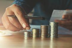Επιχειρησιακό accountin με τα χρήματα αποταμίευσης με το χέρι που βάζει τα νομίσματα επάνω στοκ εικόνες