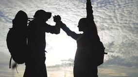 Επιχειρησιακών ταξιδιών ανδρών και γυναικών ομαδικής εργασίας η έννοια κερδίζει χέρια κουνημάτων βοήθειας σκιαγραφιών ηλιοβασιλέμ φιλμ μικρού μήκους