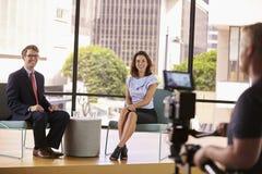 Επιδέξια ντυμένοι άνδρας και γυναίκα στο σύνολο για μια συνέντευξη TV στοκ εικόνες