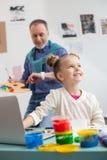 Επιδέξιος ώριμος ζωγράφος και η μικρή εγγονή του στοκ εικόνες
