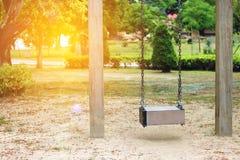 Επιλέξτε την εστίαση, κενή ξύλινη ταλάντευση στην παιδική χαρά με την επίδραση φλογών φακών στοκ εικόνες με δικαίωμα ελεύθερης χρήσης